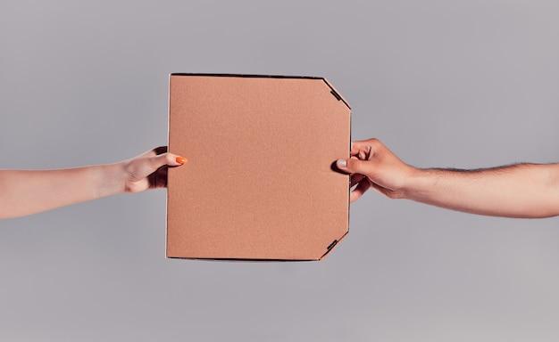 灰色の背景で隔離の顧客にピザを配達する宅配便の手のクローズアップ画像。