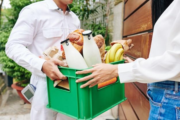 検疫のために家にいる若い女性に新鮮な牛乳、パン、果物の箱を与える配達人のクローズアップ画像