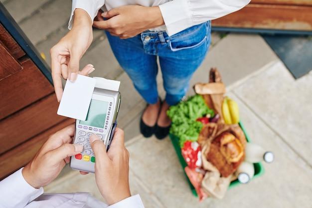 식료품 주문시 신용 카드로 결제하는 여성 고객의 클로즈업 이미지