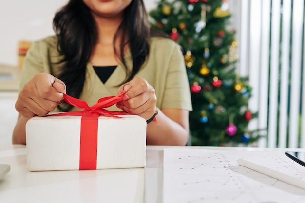 Крупным планом изображение женщины-предпринимателя, открывающей рождественский подарок за офисным столом