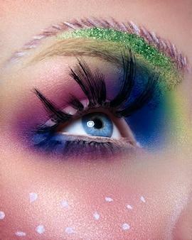 明るい色とりどりのファッションメイクで女性の目の画像をクローズアップ。