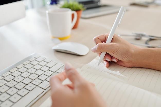 机に座ってメモ帳で書いている女性の一般開業医のクローズアップ画像