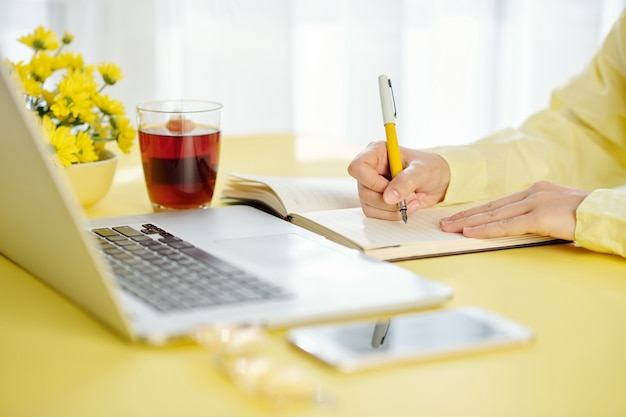 집에서 노트북에서 웹 세미나를보고 노트북에 메모를하는 여성 학생의 클로즈업 이미지