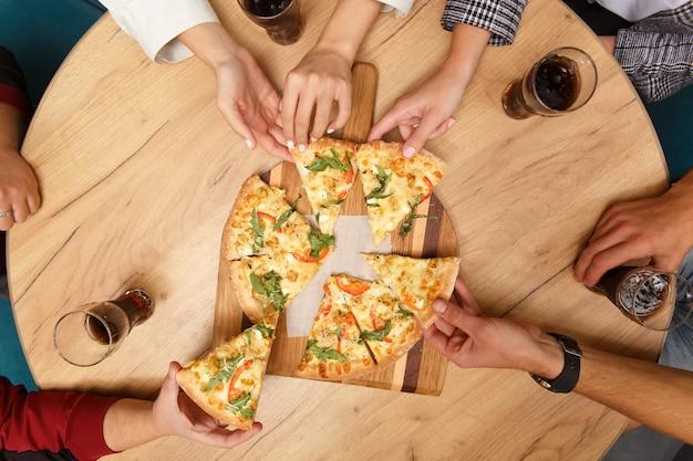 Изображение крупным планом друзей, делящих традиционную итальянскую пиццу и пьющих чай в кафе