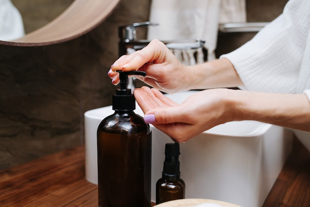 ボトルからエコ石鹸をポンピングする成熟した女性の手の画像をクローズアップ。彼女はバスルームの流しの前に立っています。