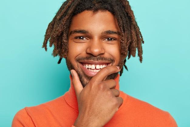 幸せな男性のクローズアップ画像は、あごに触れ、広く笑顔で、完璧な白い歯を持ち、楽しい話を楽しみ、鮮やかな服を着て、ドレッドヘアを持ち、青い背景の上に隔離されています。