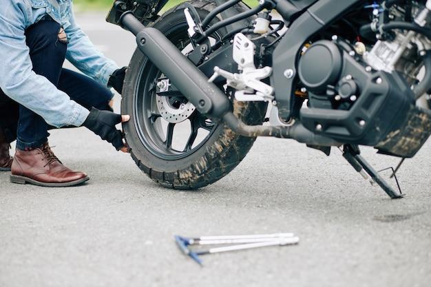 Изображение крупным планом человека, заменяющего поврежденную шину мотоцикла
