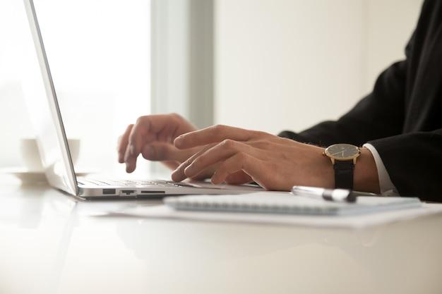 Крупным планом изображение ман руки в наручные часы, набрав на ноутбуке
