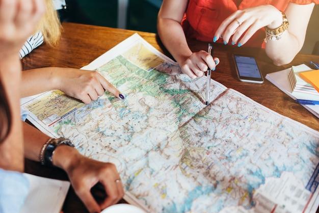 テーブルとそれを指している女性の手の上に横たわる地図のクローズアップ画像