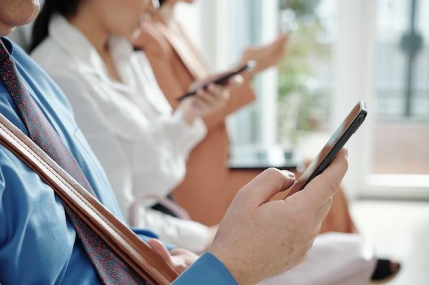 사무실 복도에 줄을 서서 스마트폰으로 문자 메시지를 읽는 성숙한 사업가의 클로즈업 이미지, 선택적 초점