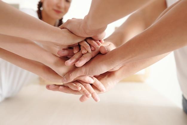 자선 센터에서 자원 봉사자로 일을 시작하기 위해 손을 쌓는 남녀의 클로즈업 이미지
