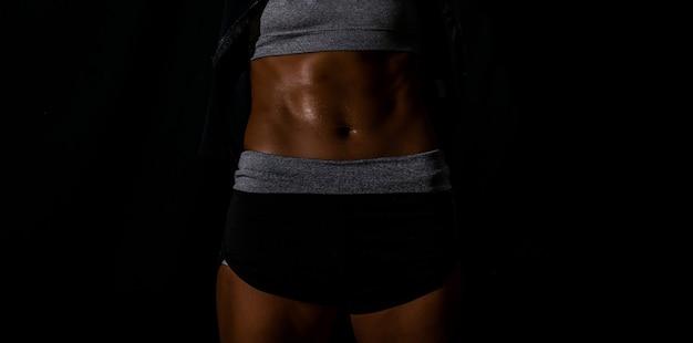 회색 배경에서 운동 후 휴식을 취하는 스포츠 의류를 입은 중동 여성의 이미지를 닫습니다