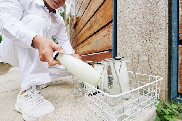 유리 우유 병을 입구 문에 배달하고 빈 빈 병을 다시 가져 오는 우유 배달원의 클로즈업 이미지