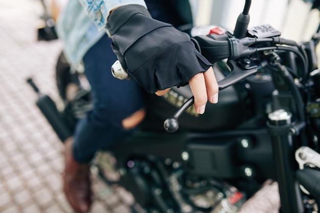 Крупным планом - мотоциклист в кожаных перчатках без пальцев, поворачивающий к нему руку, чтобы начать кататься