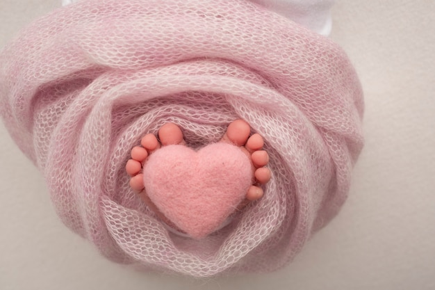 Крупным планом изображение ног новорожденного ребенка на розовом одеяле. розовое вязаное шерстяное сердце в пальцах новорожденного.