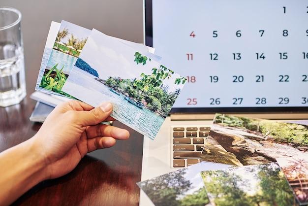 Крупный план фотографа показывает распечатанные фотографии из отпуска, который он сделал в последний месяц
