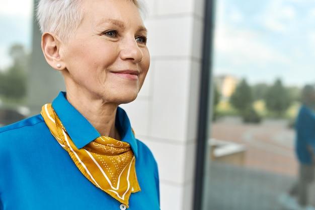웃고, 좋은 날씨를 즐기고, 파란색 셔츠와 목도리를 입고 도시 거리에 야외에서 걷는 그녀의 60 년대에 긍정적 인 아름다운 유럽 여성의 이미지를 닫습니다. 사람, 노화 및 라이프 스타일