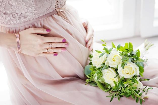 手で彼女の腹に触れる妊娠中の女性のクローズアップ画像