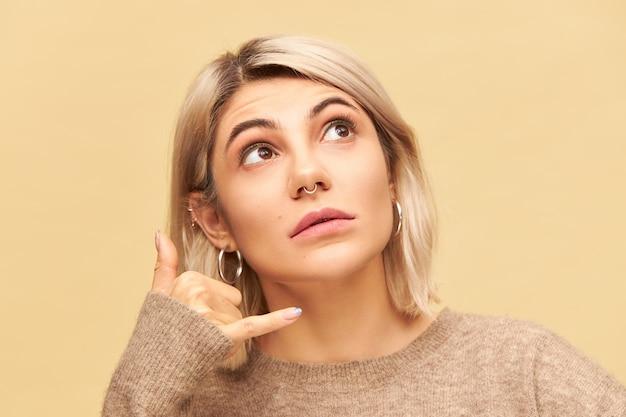 금발 밥 헤어 스타일과 코걸이를 올려다 보는 예쁜 여성의 이미지를 닫고, 엄지와 새끼 손가락으로 그녀의 귀에 손을 잡고 제스처를 만들고 전화하세요. 신체 언어