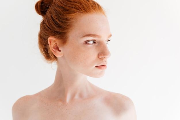 Крупным планом изображение довольно голая рыжая женщина, глядя в сторону