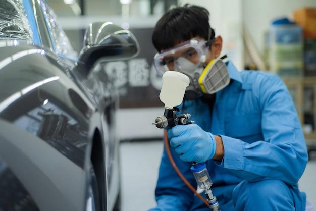 Изображение крупного плана профессиональной покраски автомобилей, акцент на переднем плане.
