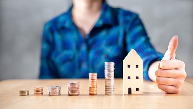 Крупным планом изображение модели сбережений и успеха денег для инвестиционного дома, дома или инвестиций в недвижимость для выхода на пенсию и концепции планирования бизнес-активов бизнес-леди