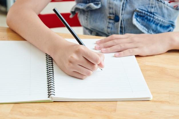 Изображение крупным планом школьницы, пишущей эссе в тетрадке за партой, или рисования эскиза для школьного проекта