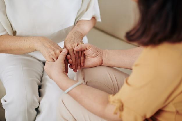 彼女を安心させようとしているときに彼女の友人の手を握っている年配の女性のクローズアップ画像