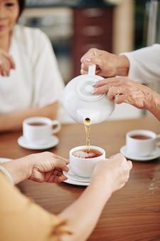 彼女の女性の友人のためにカップに熱い紅茶を注ぐ年配の女性のクローズアップ画像