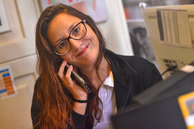 사무실에서 전화로 웃는 소녀의 이미지를 닫습니다
