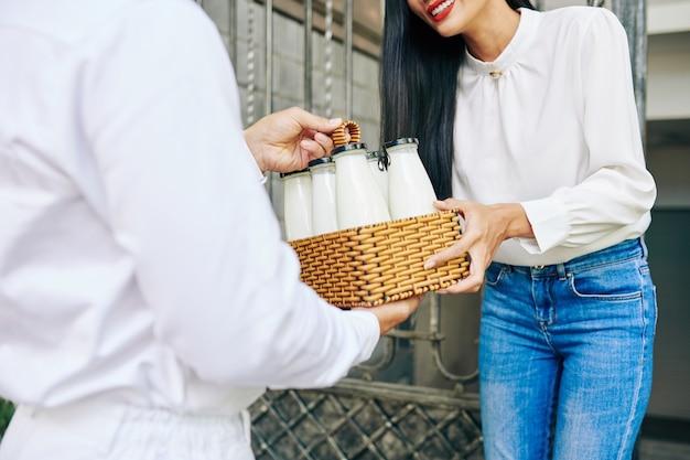 彼女の家のドアで新鮮な牛乳の注文を受けている笑顔の若い女性のクローズアップ画像