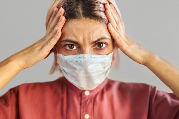 コロナウイルスのパンデミックや経済危機にうんざりしている、頭に手をつないでいる顔のサージカルマスクでストレスを感じている怖がっている若い女性の画像を閉じます。病気、ウイルス、感染、検疫、社会的距離