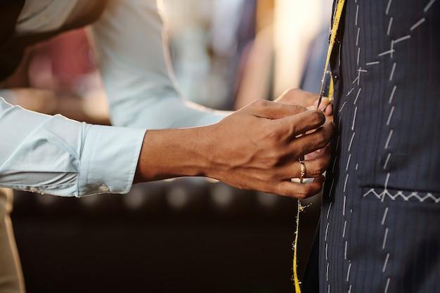 양복 재킷에 구멍이있는 버튼을 정렬하기 위해 측정 테이프를 고소하는 재단사의 클로즈업 이미지