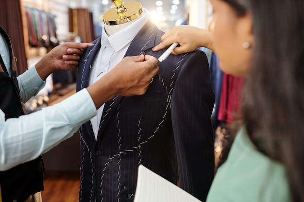 アトリエで作業する際のオーダーメイドのジャケットの襟の詳細について話し合う仕立て屋のクローズアップ画像