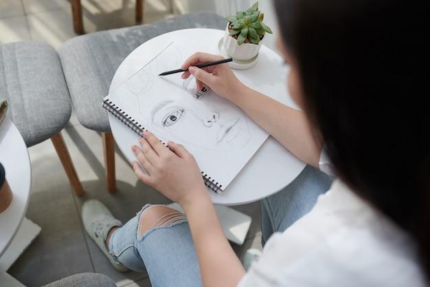 黒インクでスケッチブックに顔を描く才能のある芸術学生のクローズアップ画像