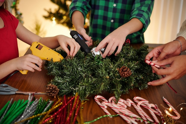 Изображение крупным планом друзей-подростков, наклеивающих безделушки на рождественский венок