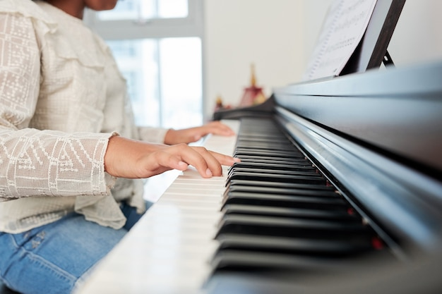 Изображение крупным планом девочки-подростка, играющей на пианино во время урока музыки в школе
