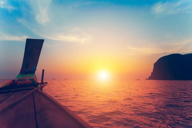 전통적인 낚시 나무 보트의 활 이미지를 닫습니다. 태국 왕국인 이국적인 피피 섬 옆에 있는 바다와 석회암 절벽 위의 숨막히는 다채로운 일몰.