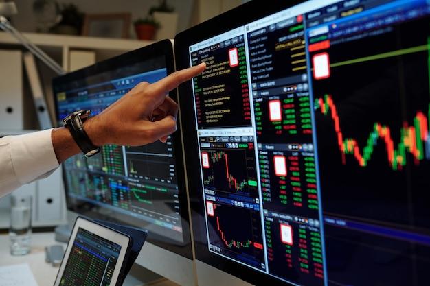 Изображение крупным планом трейдера указывает на графики на экране компьютера и анализирует данные и цены на активы