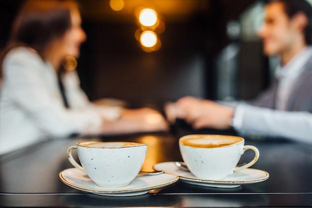 카페의 나무 테이블에 라떼와 함께 두 개의 커피 컵의 이미지를 닫습니다.