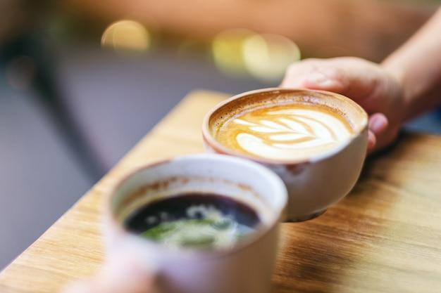 나무 테이블에 두 사람이 커피잔을 부딪치는 이미지를 닫습니다
