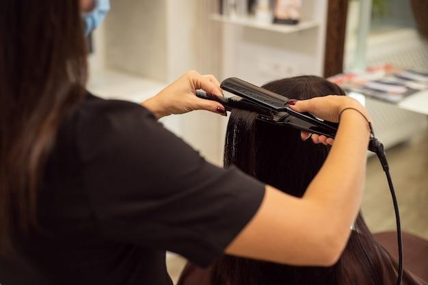 ストレートヘアアイロンを使用してヘアスタイルを作成しながら、黒い制服を着た認識できない美容師の画像をクローズアップ