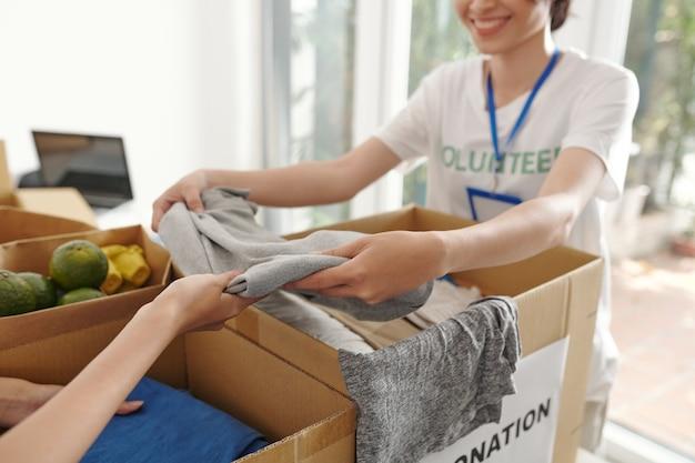 도움이 필요한 사람들을 위해 포장된 판지 상자에 따뜻한 접힌 옷을 넣는 자원 봉사자의 클로즈업 이미지