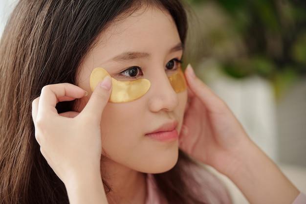 彼女のかわいい友人の目の下に保湿パッチを適用している女性のクローズアップ画像