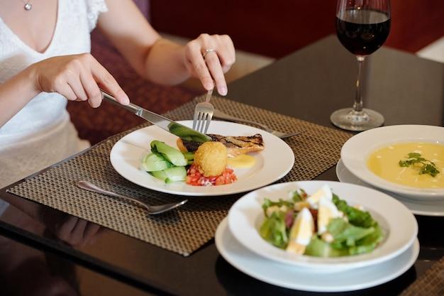 高級レストランで昼食のために揚げ魚と野菜を取得している女性のクローズアップ画像