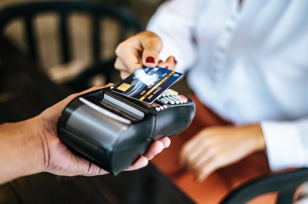 Изображение конца-вверх женщины оплачивая с кредитной карточкой в кафе