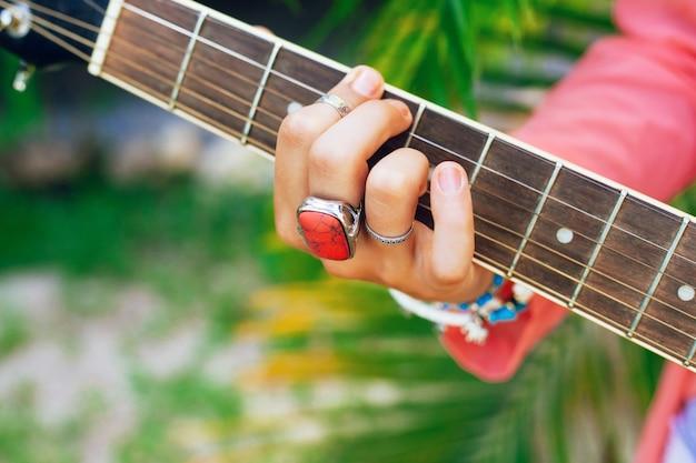 アコースティックギター、明るいアクセサリー、緑のヤシの木の背景で遊ぶ女性の画像を閉じます。