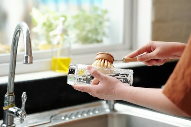 Крупным планом изображение женщины, использующей экологически чистую щетку при мытье посуды в кухонной раковине