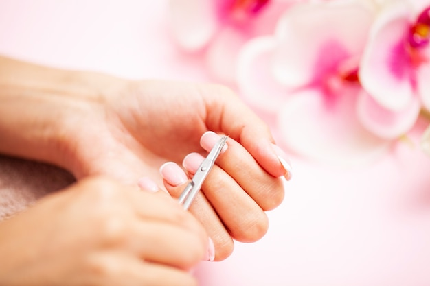 매니큐어를 할 때 네일 버퍼를 사용하여 집에서 손톱을 연마하는 여성의 이미지를 닫습니다.