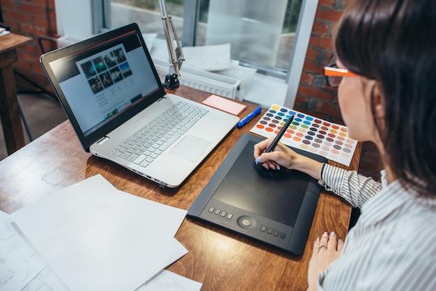 그래픽 태블릿과 현대 사무실에 앉아 노트북을 사용하여 프로젝트를 그리는 여성의 클로즈업 이미지.